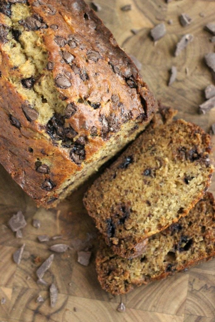 banana bread on a cutting board with dark chocolate chips